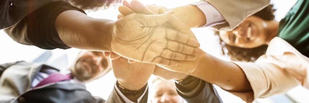 Teambild mit Händen in der Mitte