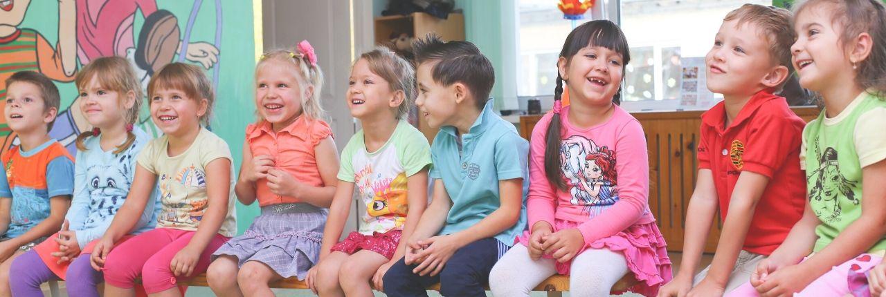 Kindergartenkinder sitzen in einer Reihe