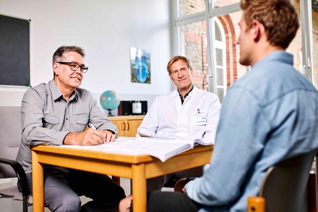 Arzt und Therapeut mit stotterndem Patienten